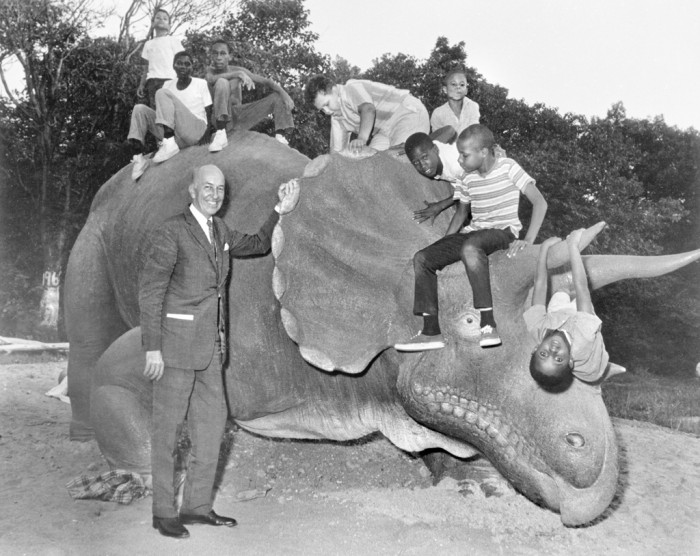 "Secretary S. Dillon Ripley (1964-1984) and unidentified children with ""Uncle Beazley,"" the Triceratops model used in the NBC TV film ""The Enormous Egg,"" at the opening of the Anacostia Neighborhood Museum on September 15, 1967. Uncle Beazley was placed in the parking lot adjoining the Carver Theater, the site of the first Anacostia Museum. Uncle Beazley was later moved to the Mall in front of the National Museum of Natural History and then to the National Zoological Park. (Photo via Smithsonian Institution Archives.)"