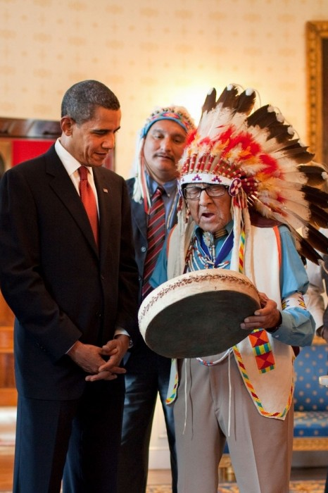 Joseph Medicine Crow, wearing feathered headdress, beats a drum while President Obama looks on.