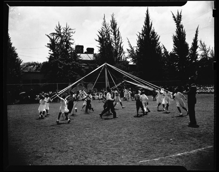 Afircan American children dance around a maypole