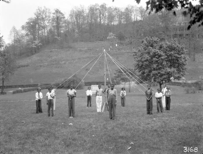 African American boys around stand around a maypole