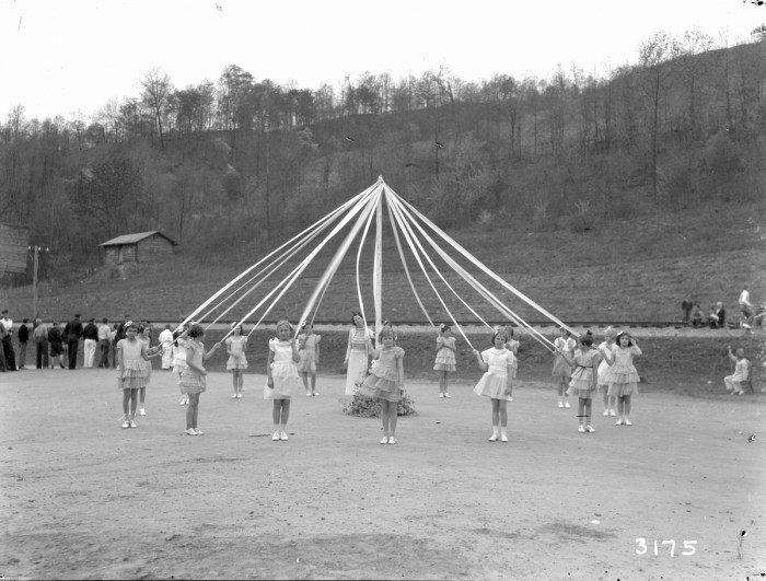 Caucasian girls stand around a maypole