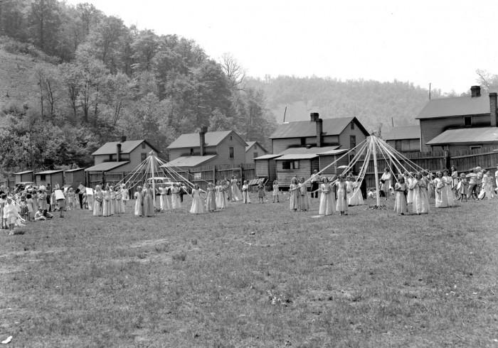 Women dancing around maypoles in a coal town