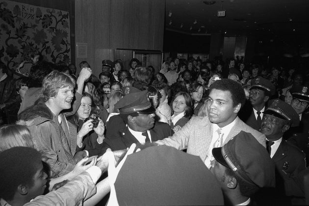 Ali surrounded by fans and security guards