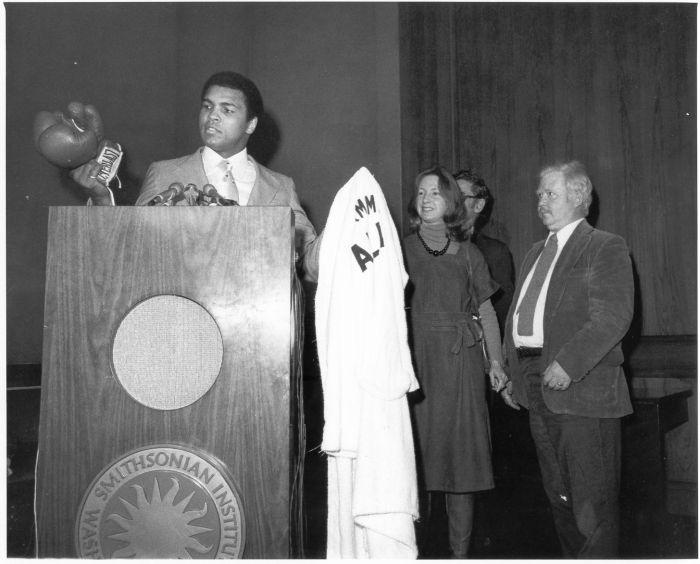 Ali at podium with gloves and robe