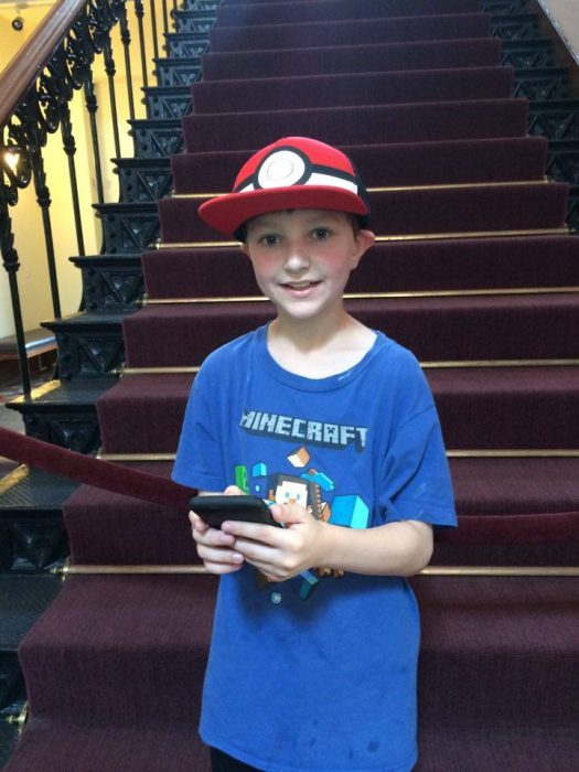 Young boy with PokeBall cap holding phone