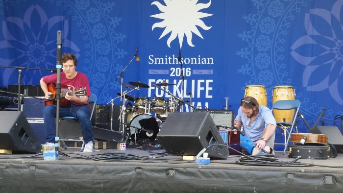 Two musicans on stage, one sitting on the floor with a harmonium