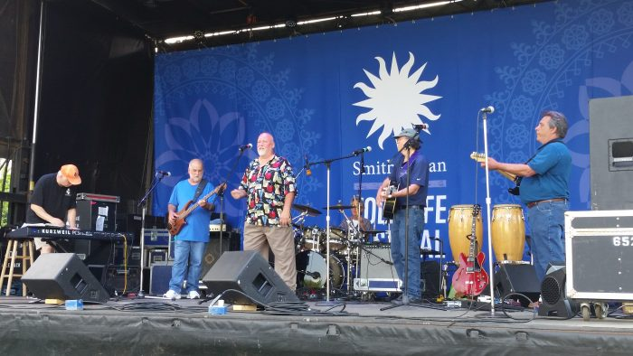 Band performing on stage, Smithsonian logo in background