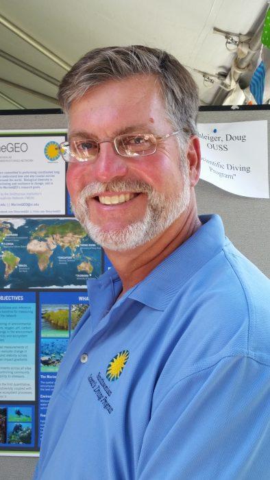 Smiling man in blue Smithsonian shirt