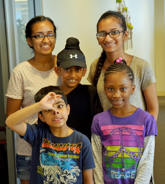 Five kids pose for a picture; four are smiling, one boy makes a face for the camera