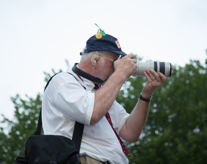 Photographer wearing hat with camera seen in profile