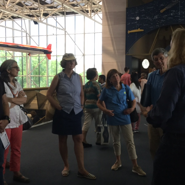 Group listens attentively to curator in the foreground. Milestone of Flight Hall is in the background
