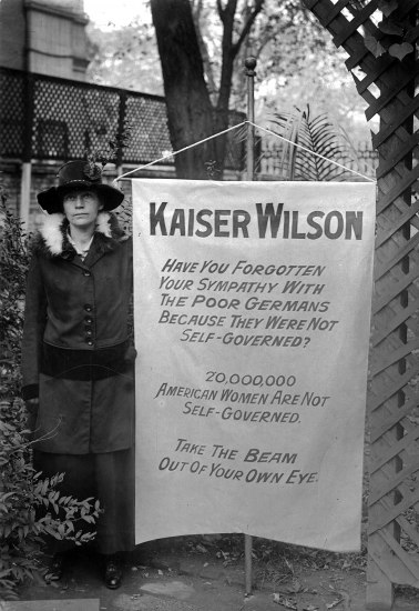Woman with banner reading Kaiser Wilson, Have you forgotten your sympathy with the poor Germans because they were not self-goverened? 20,000,000 American women are not self-governed. Take the beam out of your own eye.