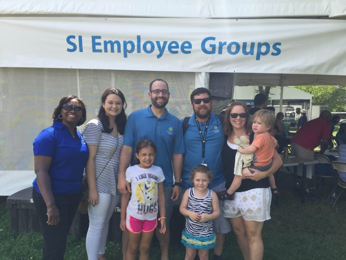 Smiling adults and children pose in front of the SI Employee Groups tent.
