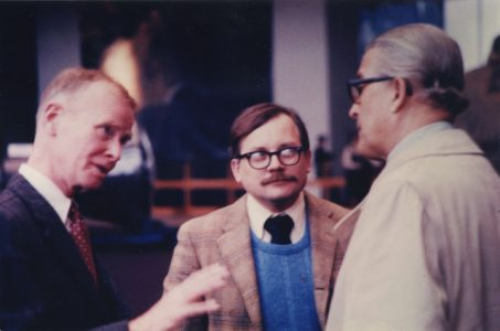 Two men in profile with Crouch listening attentively