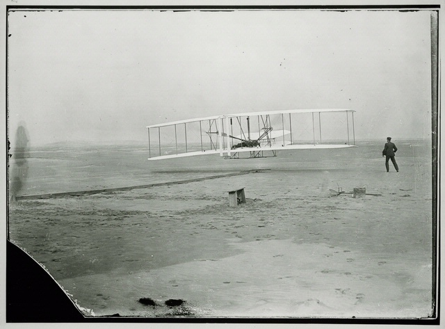 Historic B&W photo of biplane on the beach