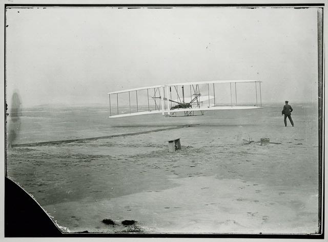 Historic B&W photo of biplane on the beach