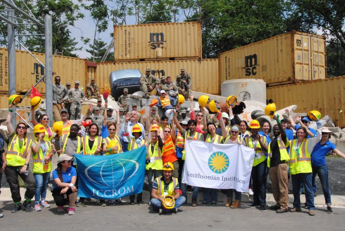 Group photo of particpants waving hard hats and holding Smithsonian and ICCROM flags