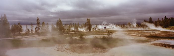 Panoramic view of geysers under cloudy sky