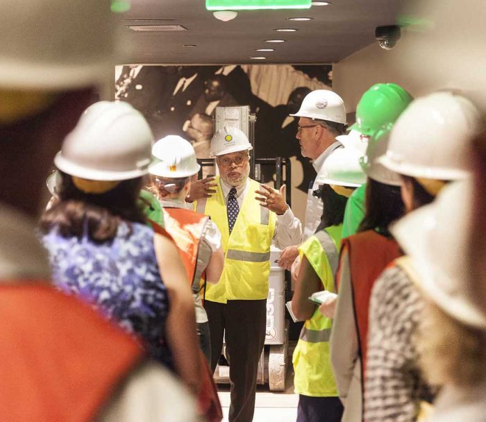 Bunch, in hard hat, facing camera while others with backs to camera listen