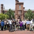 Group poses with hands raised (one jumping) with Haup Garden and south side of the Castle in the background