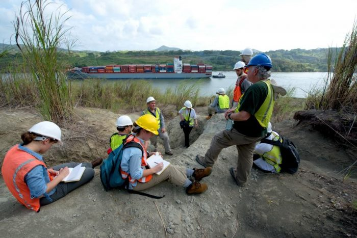 People in hard hats and vests take notes on the bank of the Panama Canal with a cargo ship in the background