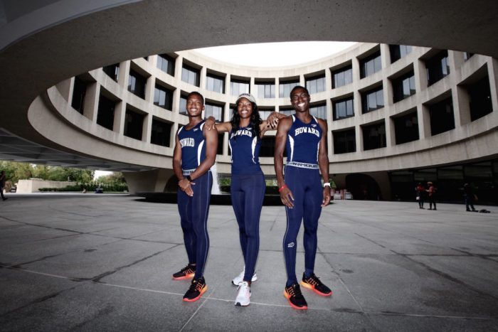 Three runners in track suits pose in museum's central atrium