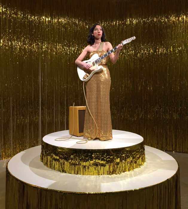 WOman in gold dress holds a guitar atop adais covered with gold foil