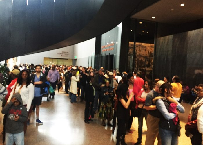 People in line in crowded gallery at African American history and Culture Museum