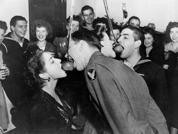 Woman and serviceman bite at apple dangling from a string
