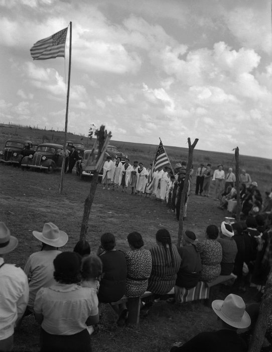 Black and white photo of pow wow, American flag in center of circle