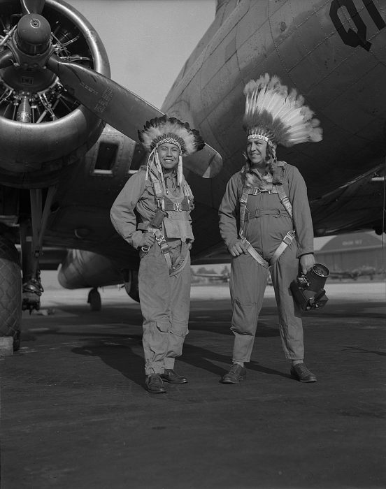 Two men in jumpsuits and eagle feather war bonnets stand in front of military plane