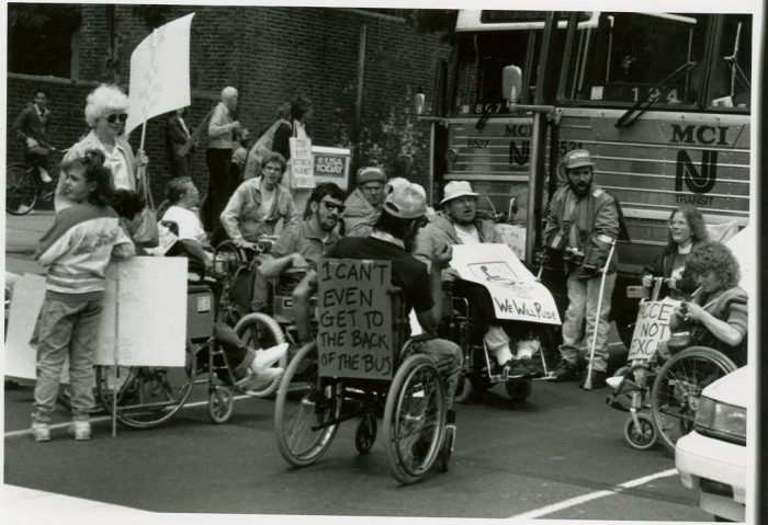 Protesters in wheelchairs carrying signs