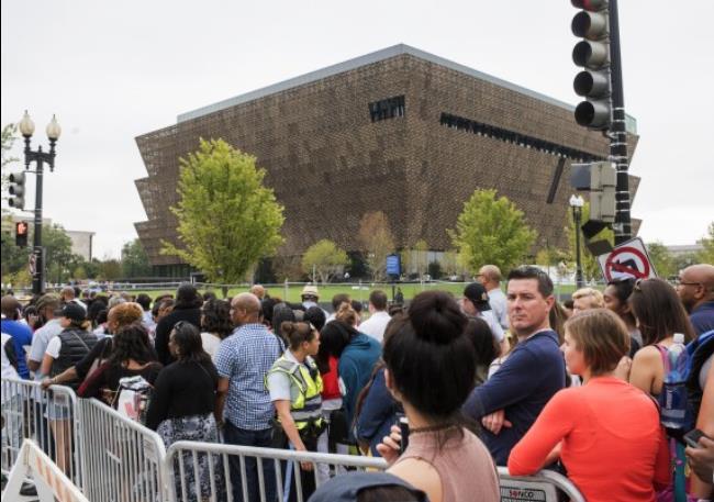 crowds behind barricades, museum in background