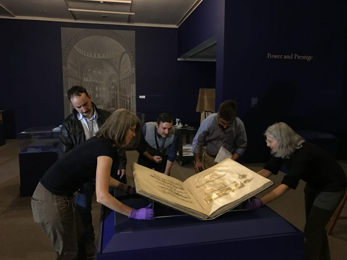 Group carefully placing large Qur'an on display mount in gallery