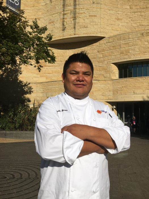 Bitsoie poses in chef's whites in front of the American Indian Museum