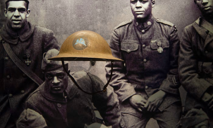 Helmet in display case woith photo of soldiers in the background