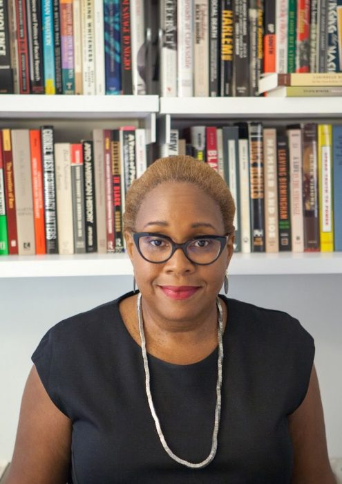 Portrait of Wilson wearing black dress and glasses, bookshelves behind her