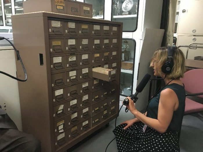 Megan, with mic and headphones, kneeling in front of file cabinet