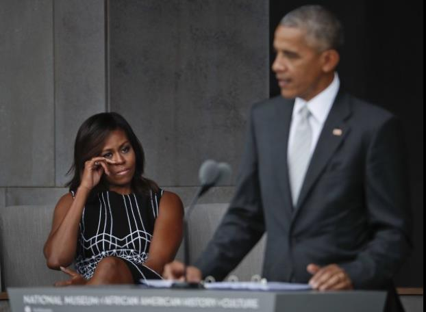 Mrs Obama wipes away a tear; president at podium in foreground