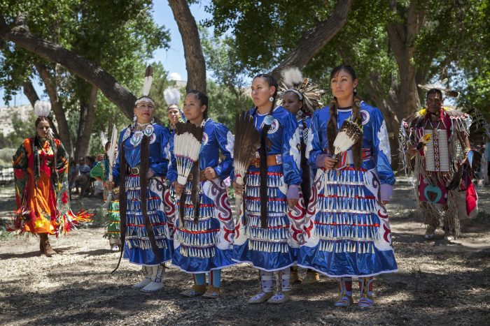 Women in Native dress stand at attention