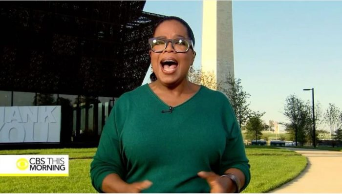Winfrey in green sweater and glasses in front of museum