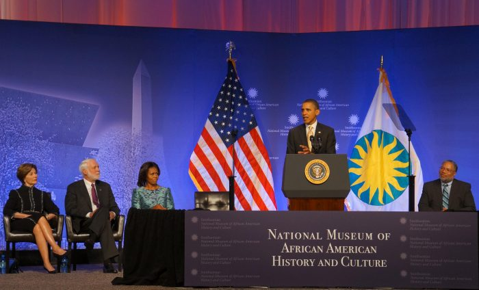 President Obama at podium, American and Smithsonian flags in the background