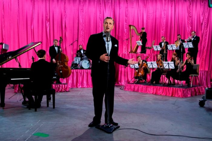 Still image showing artist at mic with orchestra and hot pink curtain behind him