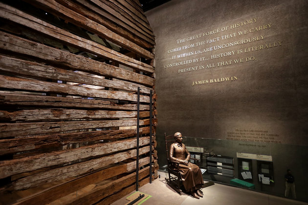 Bronze statue seated in rocking chair next to preserved cabin