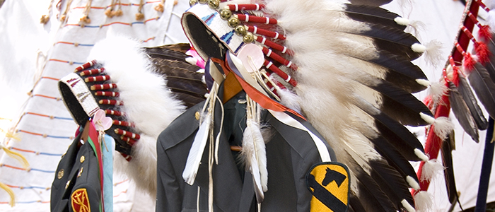 cropped banner featuring military uniforms draped with eagle feather bonnets