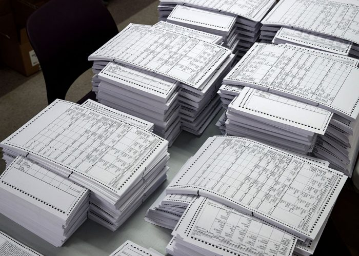 Stacks of paper ballots on table