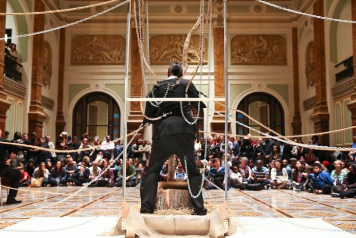 Sheldon, with chains attached, performs in front of audience seated on floor