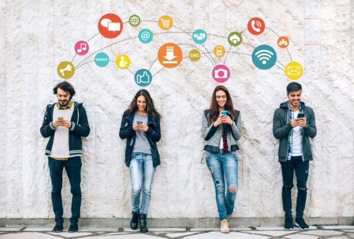 Four young people on phones with social media icons above them