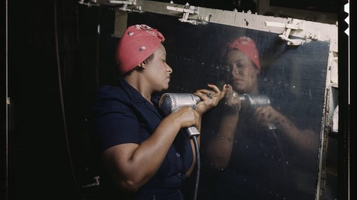 African American woman in head scarf drilling rivets
