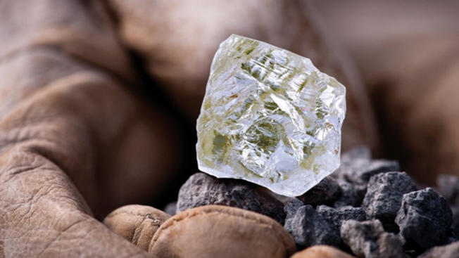 Close up of large uncut diamond held in person's hand